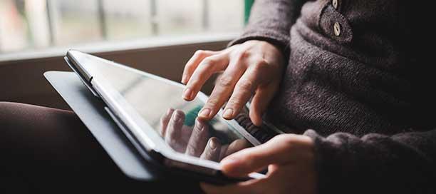A mão de uma pessoa usando um iPad perto de uma janela.