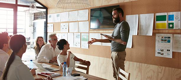 Homem liderando um workshop presencial com uma equipe de pessoas