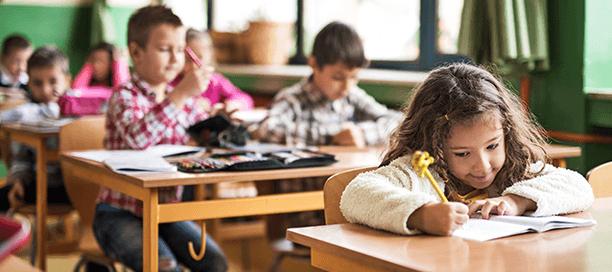 Crianças fazendo trabalhos escolares na sala de aula.