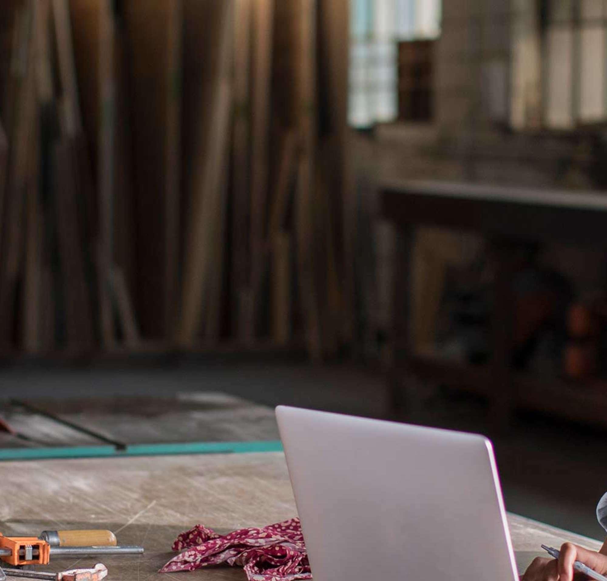 Mulher jovem trabalhando no computador, em sua loja de madeiras