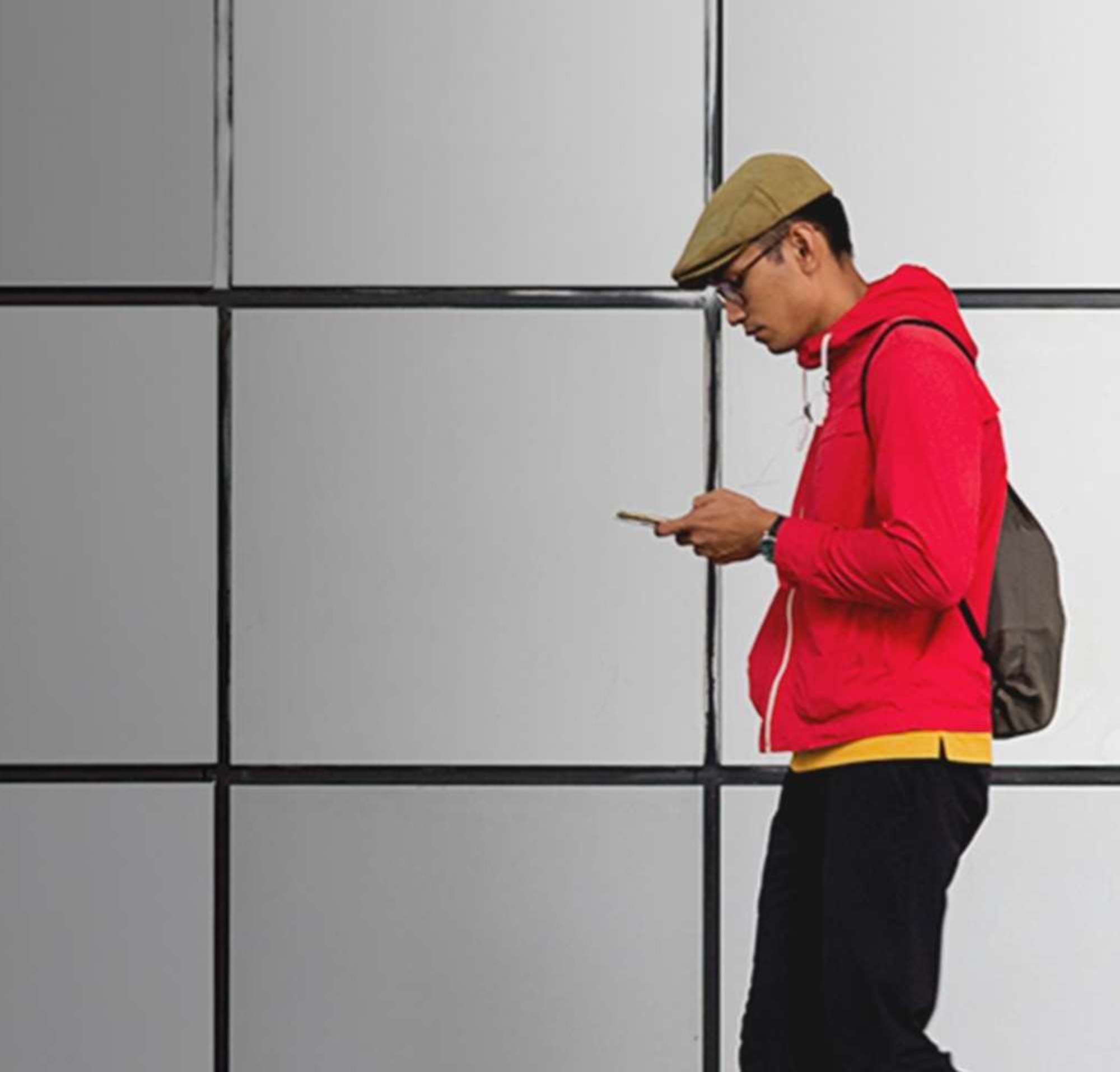 Homem caminhando ao lado de janelas grandes, olhando para o celular.