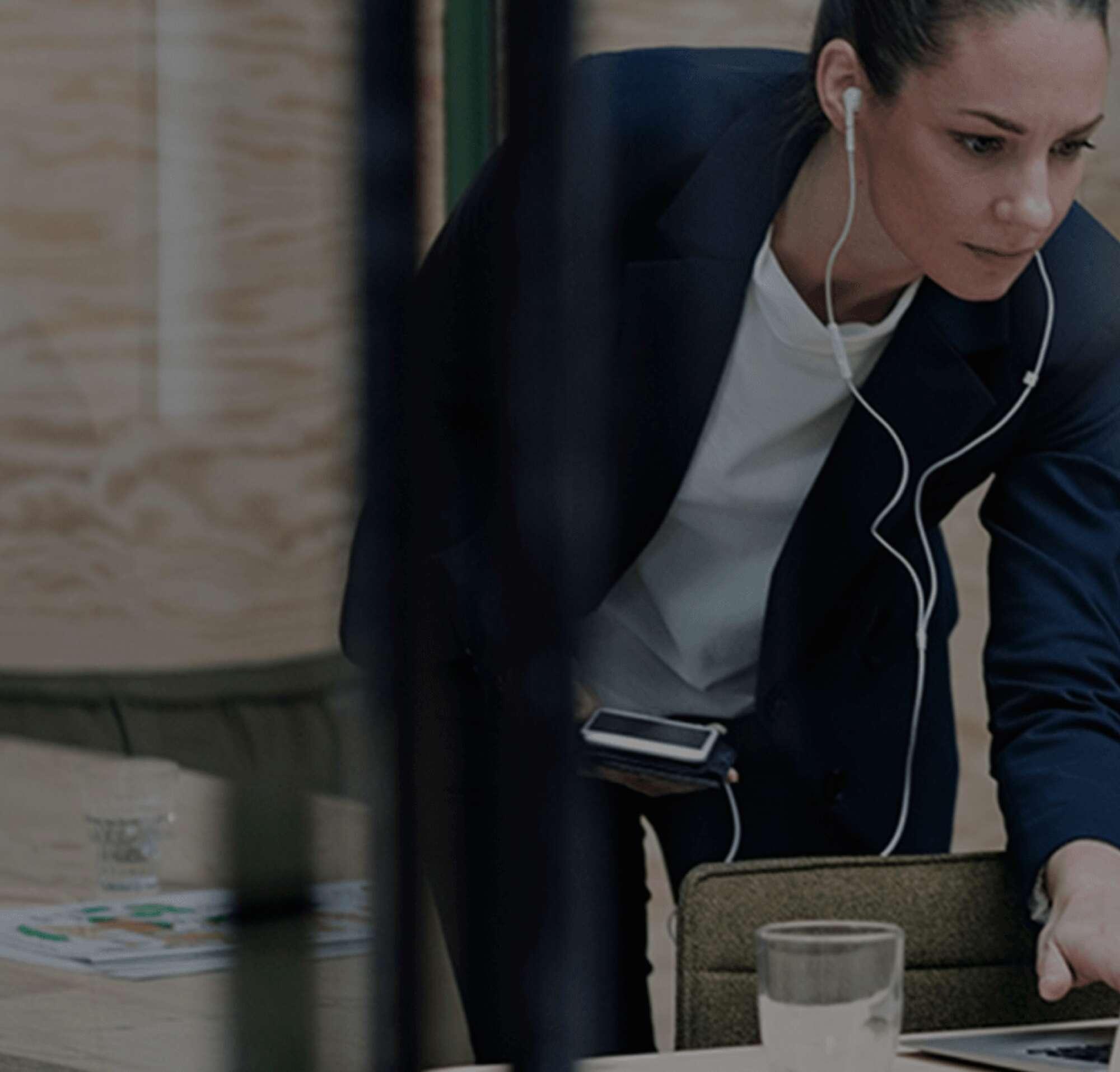 Mulher com fones trabalhando em um laptop e segurando seu telefone.