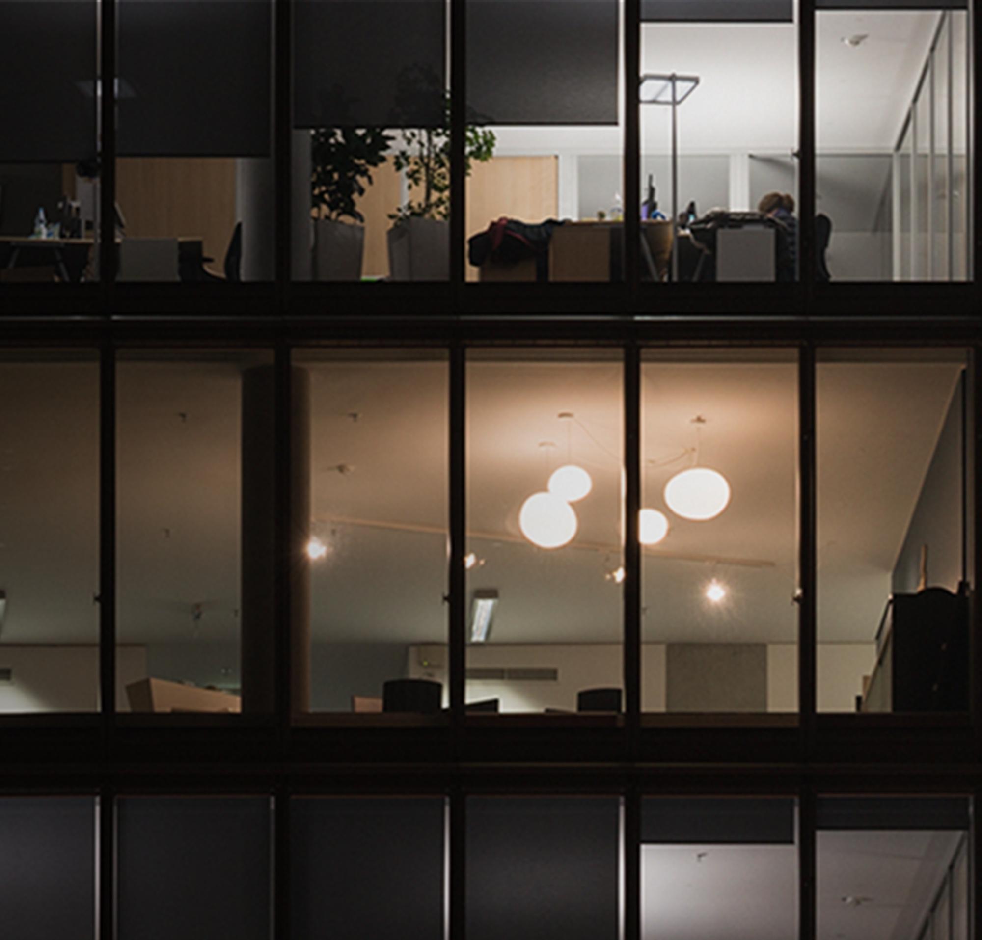 Uma imagem de três andares quase totalmente escuros em um prédio de escritórios de vários andares à noite.