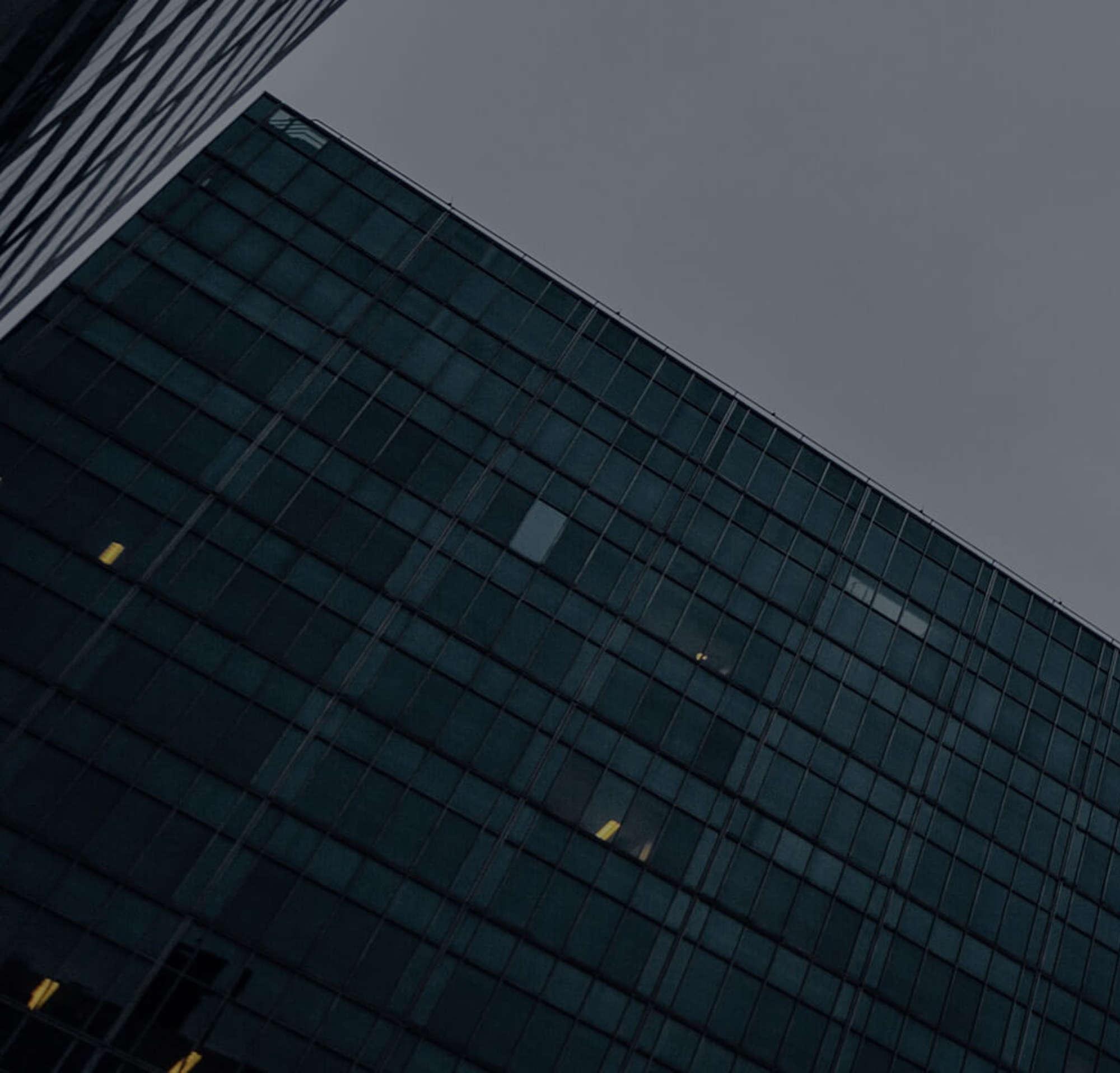 Uma foto da base de um arranha-céu e outro prédio comercial à luz da noite em um dia nublado.