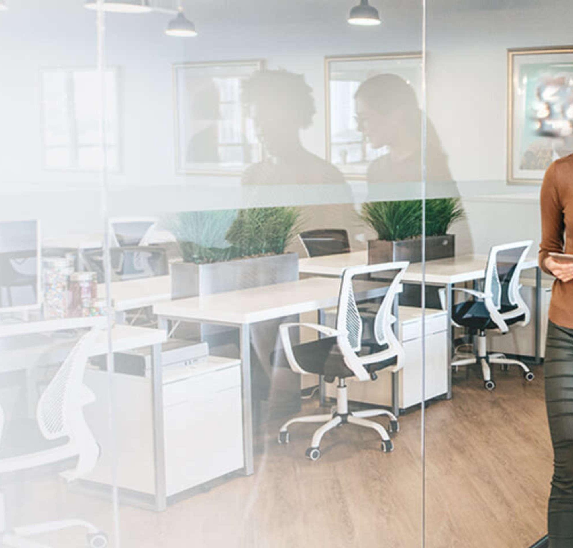 Duas mulheres em uma sala de reunião andando e conversando enquanto olham para um documento.