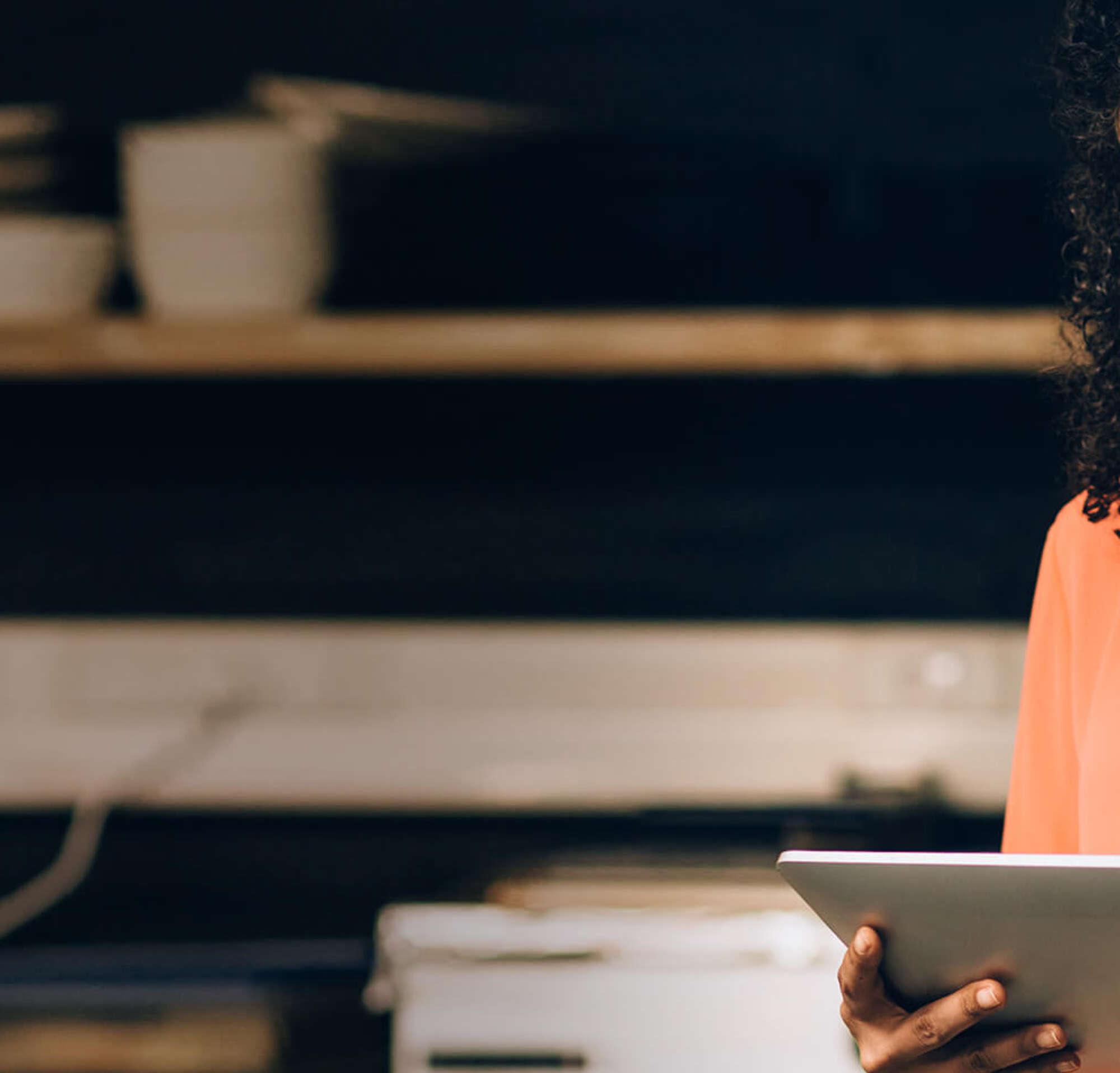 Mulher em uma cozinha escura de restaurante, olhando para um tablet
