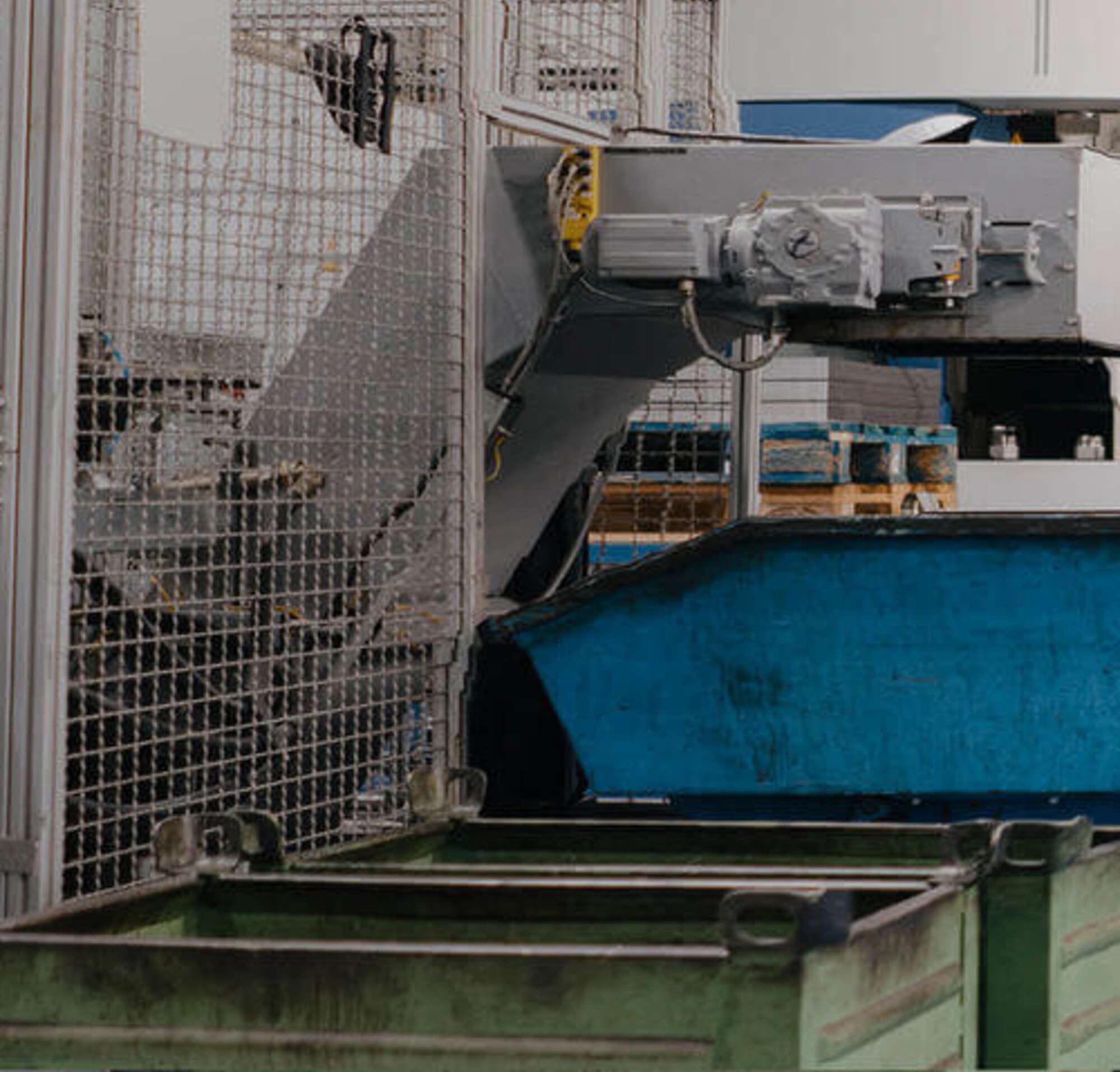 Um homem de terno andando com um operário dentro de uma fábrica com grandes máquinas