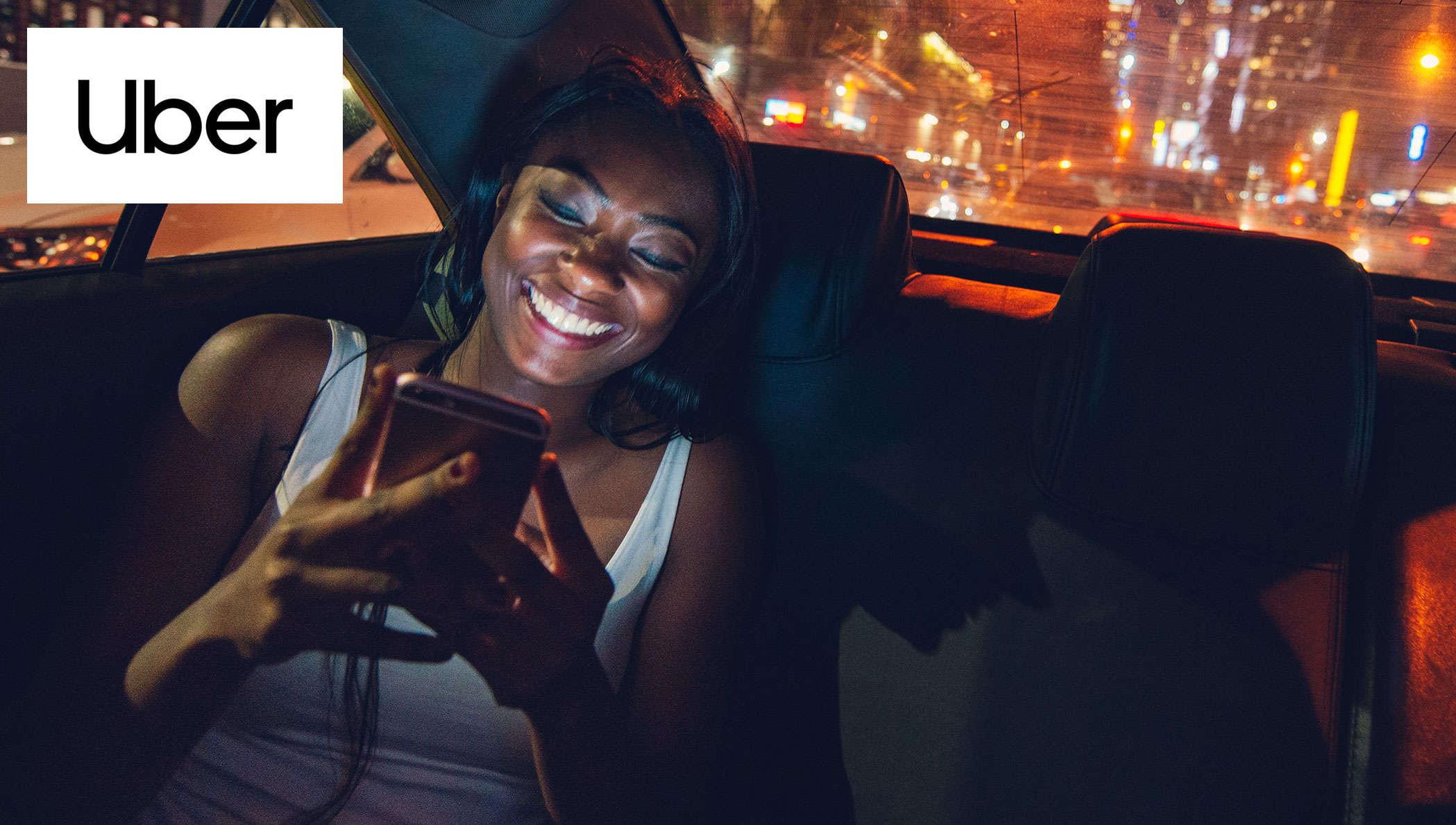 Logotipo da Uber com fundo de pessoa no celular dentro do carro