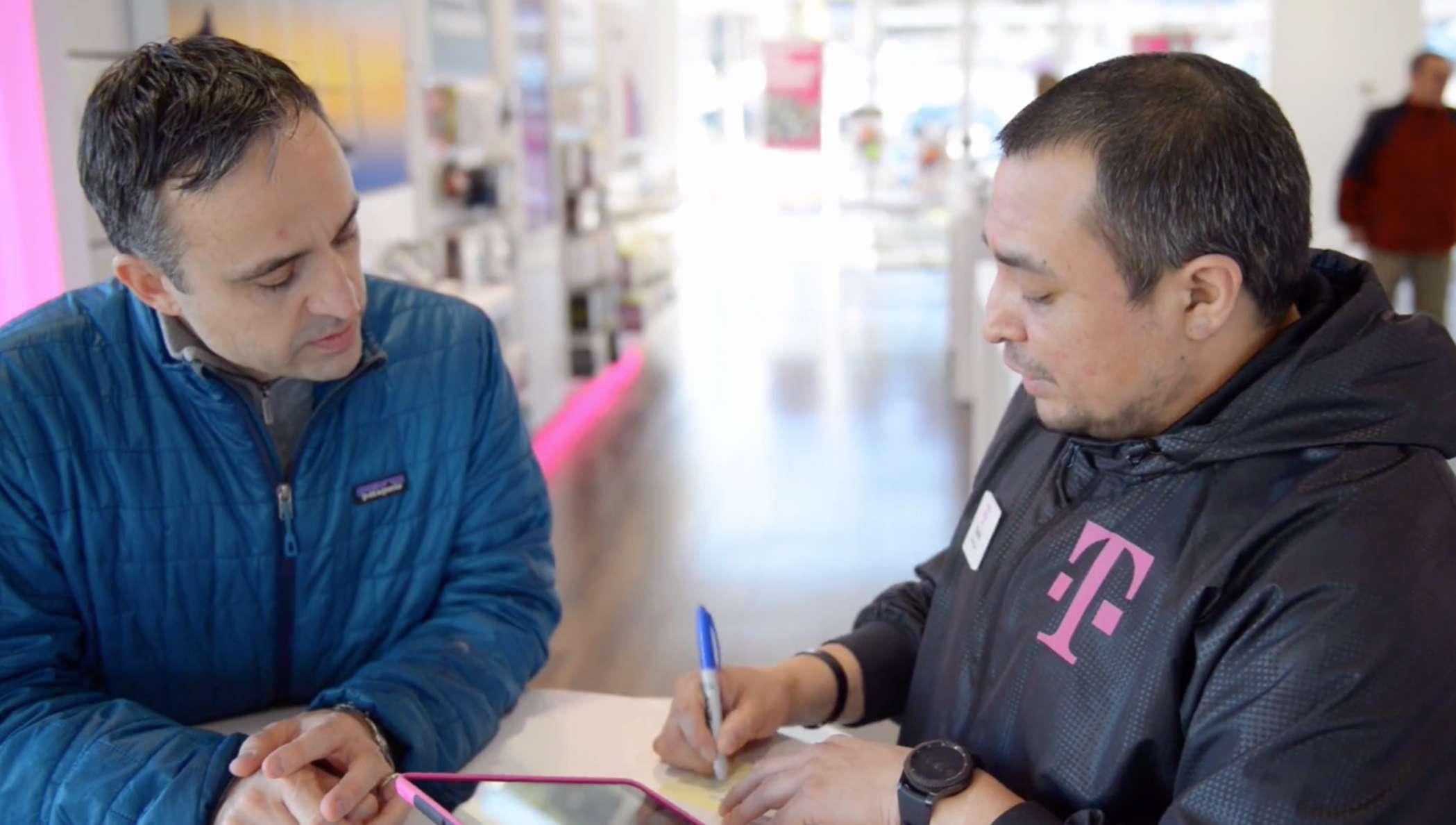 Duas pessoas em uma loja da T-Mobile trabalhando em um contrato de celular.