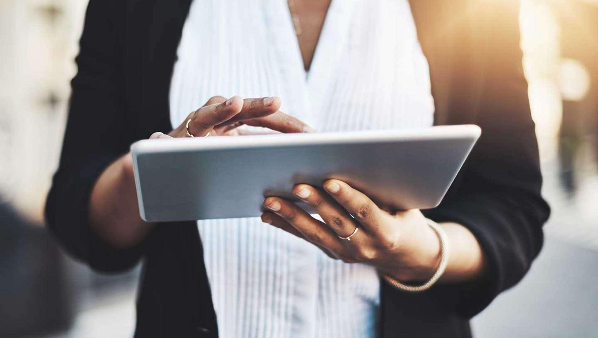 Uma executiva conferindo informações sobre um documento para assinar em seu tablet