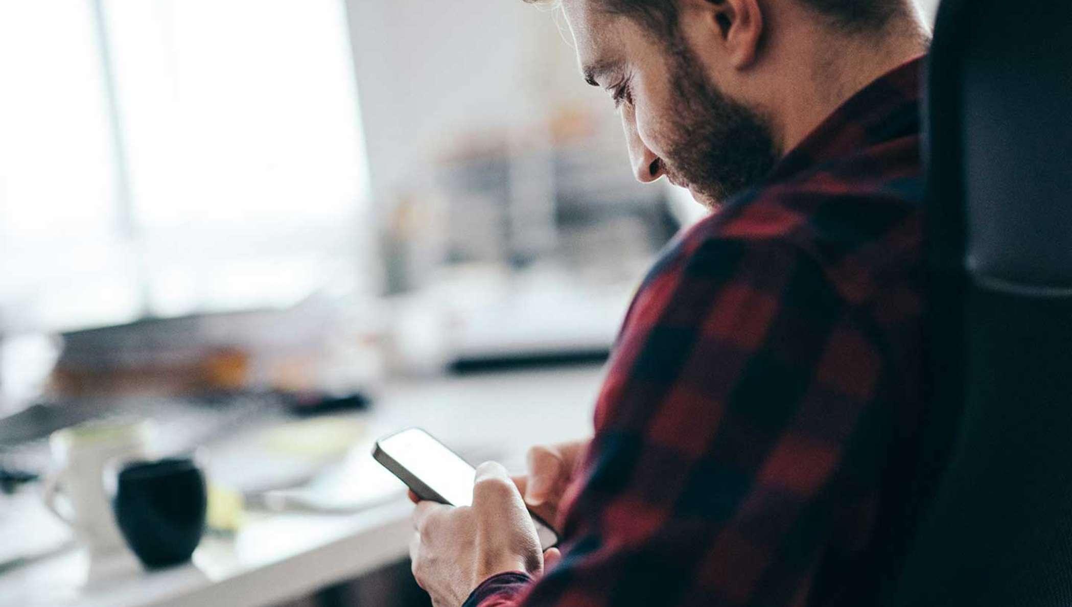 Um homem com barba em uma blusa de flanela xadrez, conferindo o status de uma assinatura em seu celular.