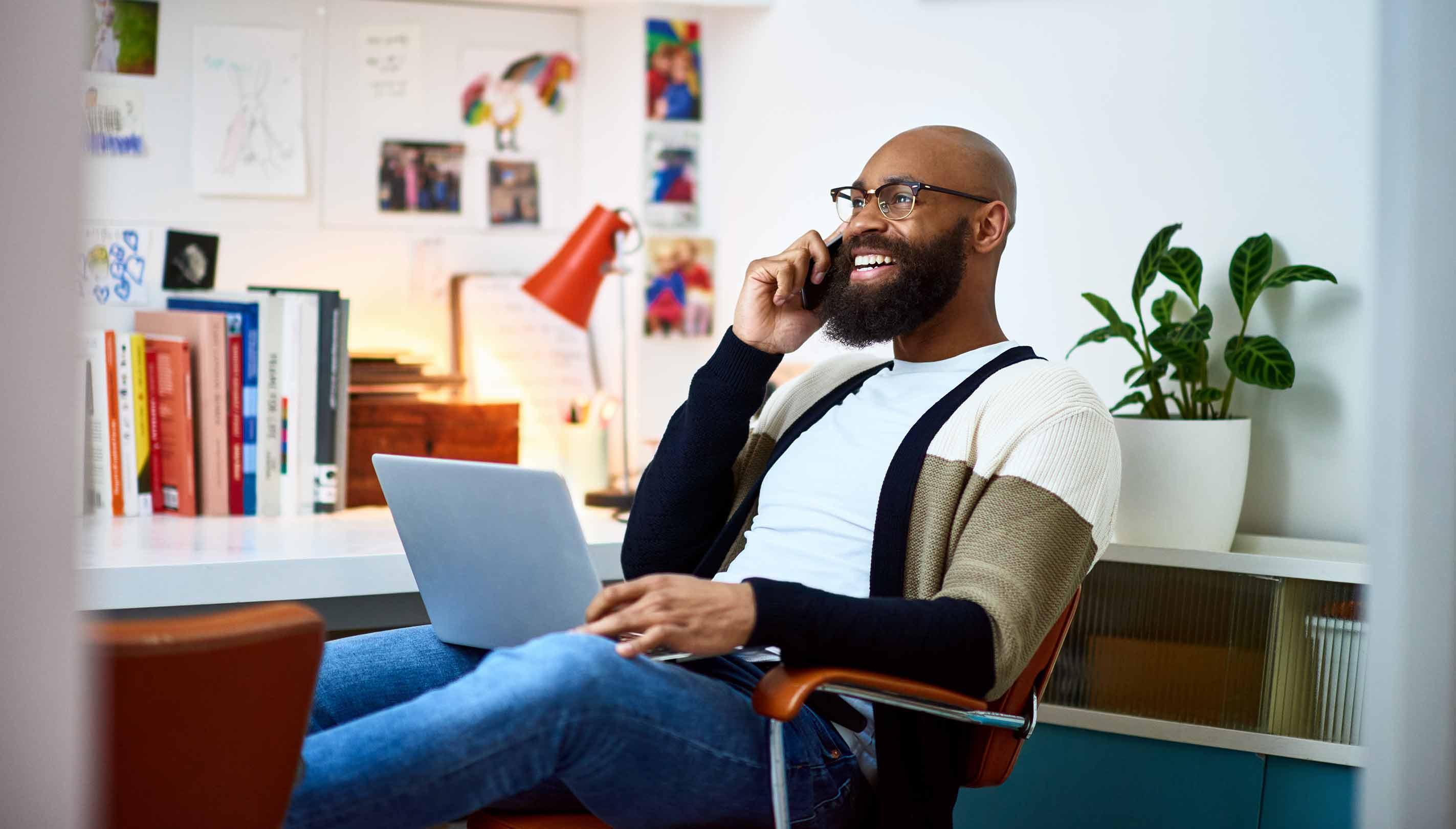 Homem sorrindo enquanto trabalha em casa de seu escritório